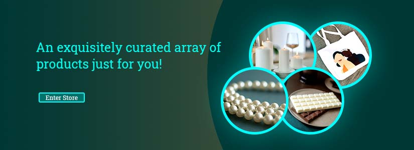 A clickable banner with a green background and images of products such as chocolates, bags, jewellery and candles depicting different product categories. Text on it reads 'An exquisitely curated array of products just for you.' The banner redirects you to the online store.